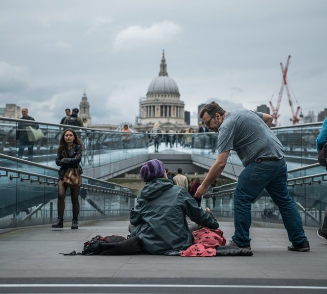 Man giving back to a poor man on the street   Source: Unsplash