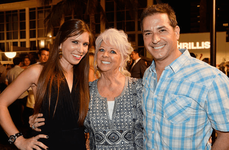 """Claudia Deen, Paula Deen, and Bobby Deen pose together during an appearance at the """"Thrillist's BBQ & The Blues"""" for the Food Network South Beach Wine & Food Festival, on February 22, 2014, in Miami Beach, Florida 