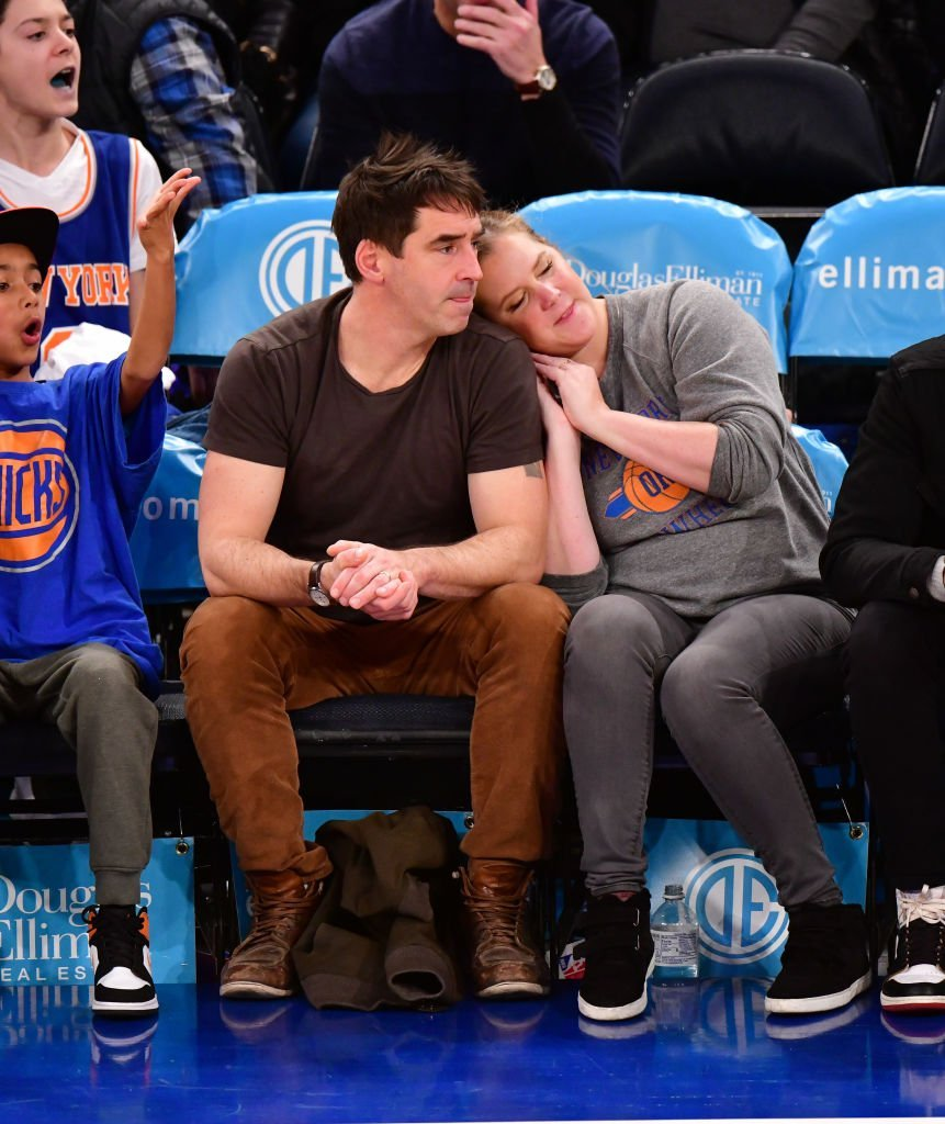 Amy Schumer leans on her husband Chris Fischer's shoulder while watching a basketball game for the Washington Wizards versus New York Knicks game, at Madison Square Garden on December 23, 2019, New York | Source: James Devaney/Getty Images