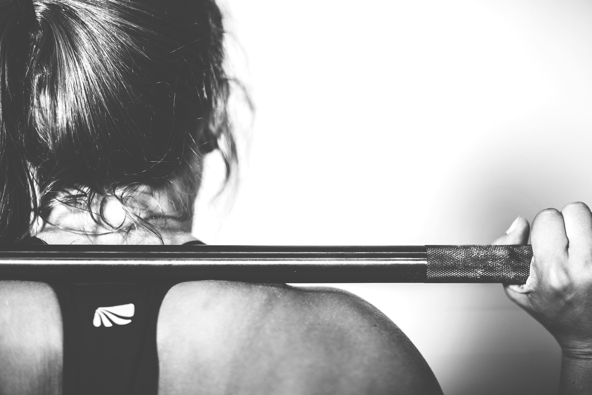 A black-and-white image of a woman working out while balancing a weight   Photo: Pixabay/Ichigo121212