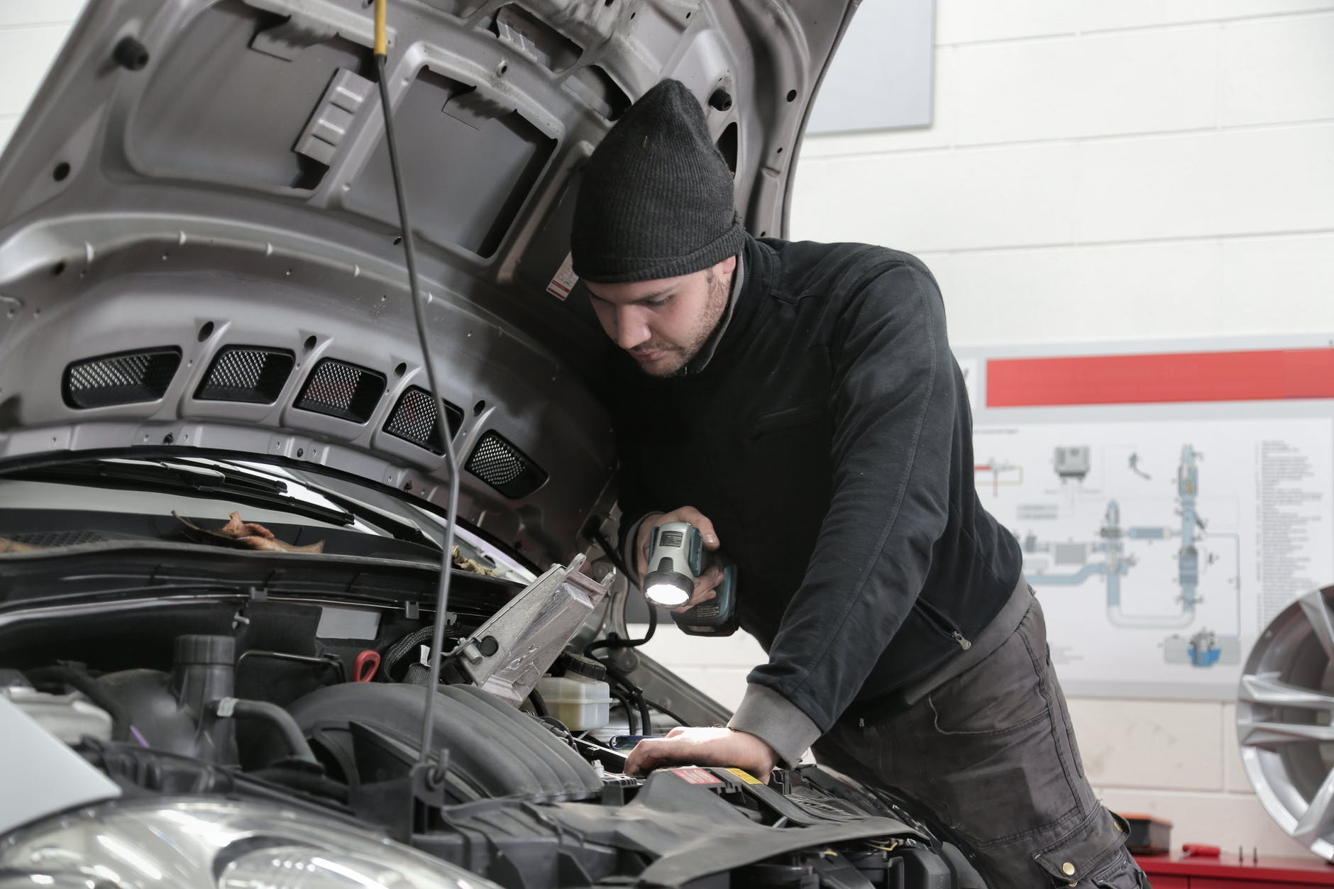 Man inspecting the car's engine.   Photo: Pexels