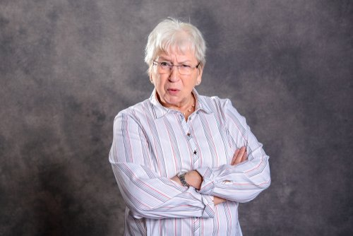 An older lady standing with her arms crossed looking angry. | Source: Shutterstock.