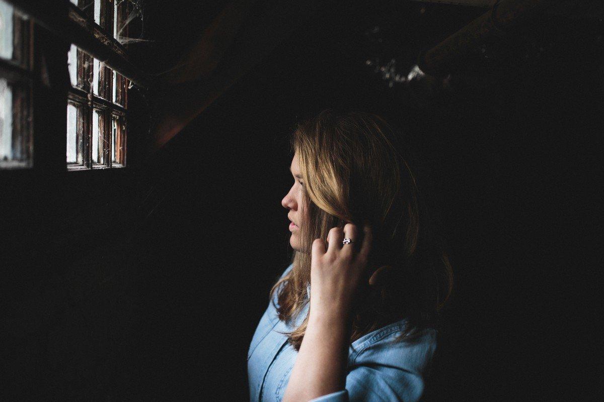 Mujer asustada viendo por una ventana. | Imagen: PxHere