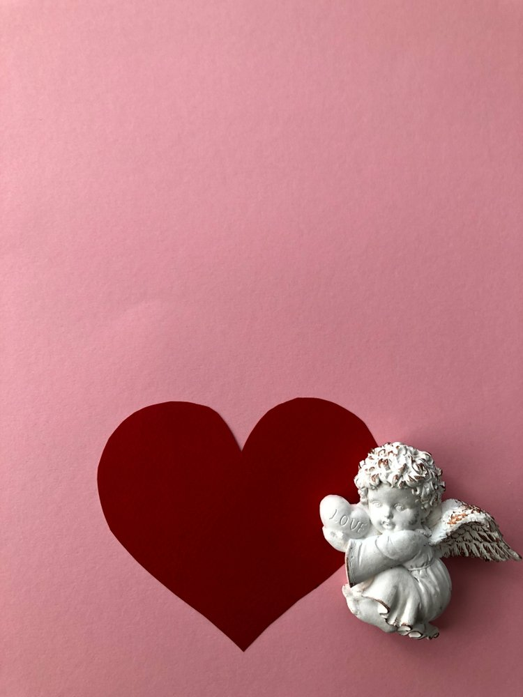 Angel baby artwork on a pink background with a red heart | Photo: Shutterstock/Assa2215