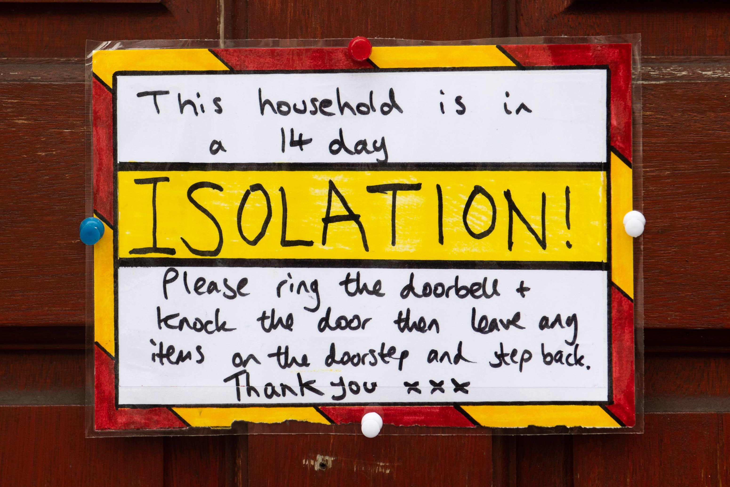 A sign on the door of a residential property where the household are in a 14 day isolation in accordance with new government guidelines on March 18, 2020 in Cardiff, United Kingdom. | Source: Getty Images