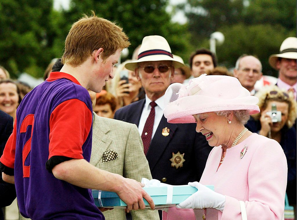 Queen Elizabeth II makes a presentation to Prince Harry after a polo match during Royal Ascot on June 18, 2003, in Windsor, England | Photo: Anwar Hussein/Getty Images