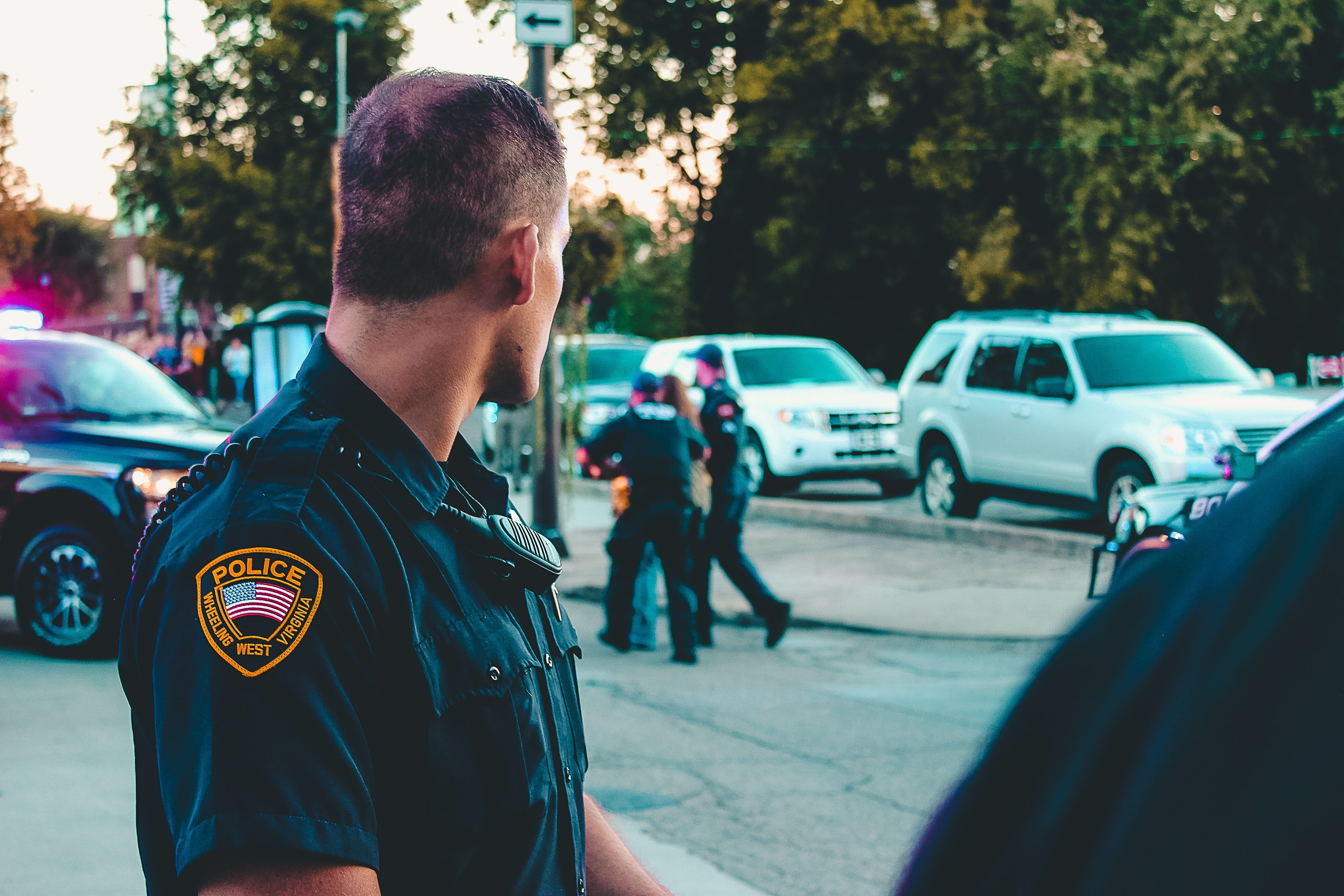 A police officer looks back towards a vehicle behind him.   Pexels/ Rosemary Ketchum