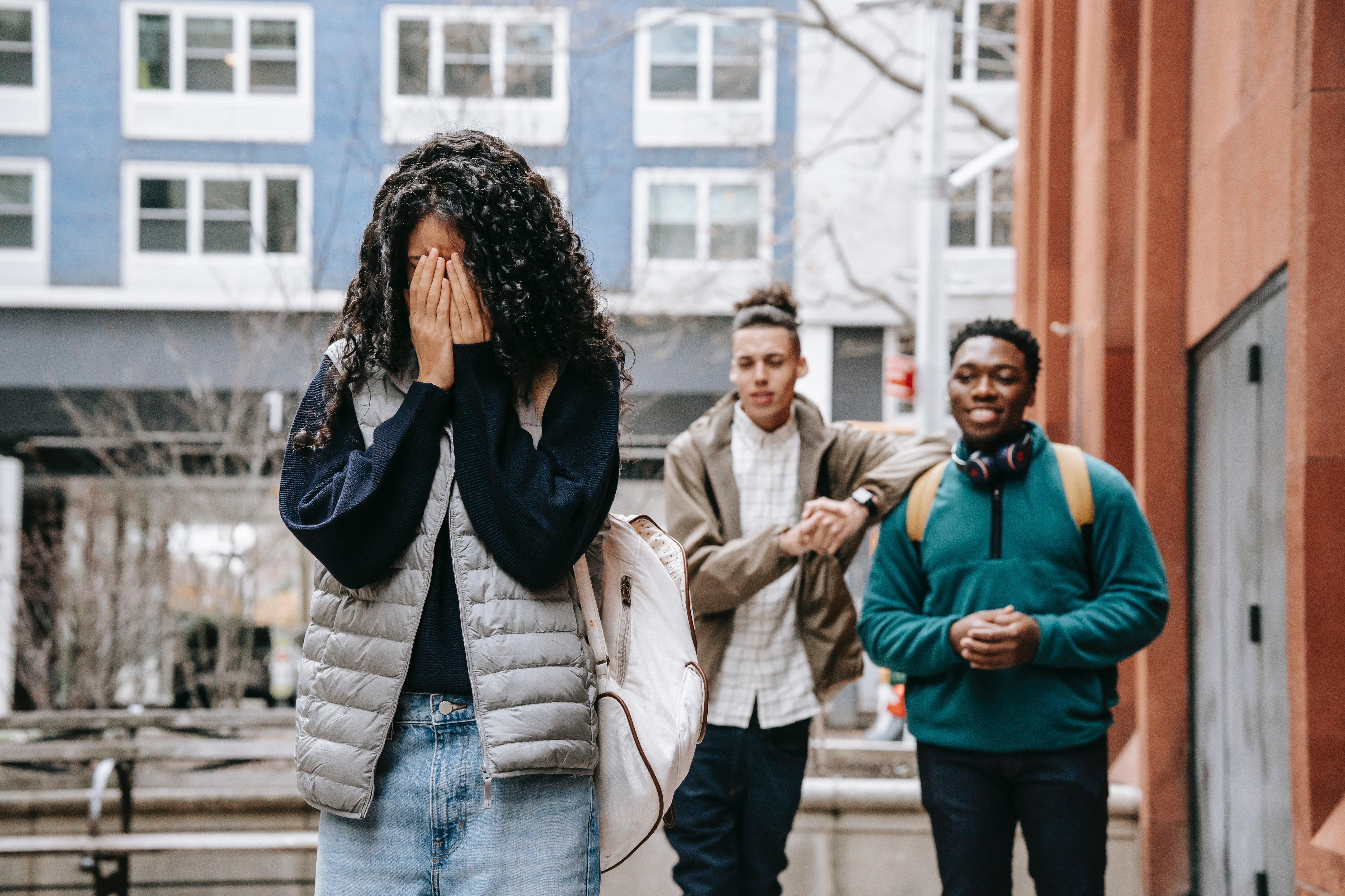 Pictured - Two male teens bullying a young woman who covers her face | Source: Pexels
