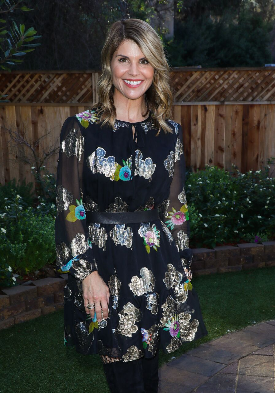 Lori Loughlin smiles in a floral black dress. | Source: Getty Images