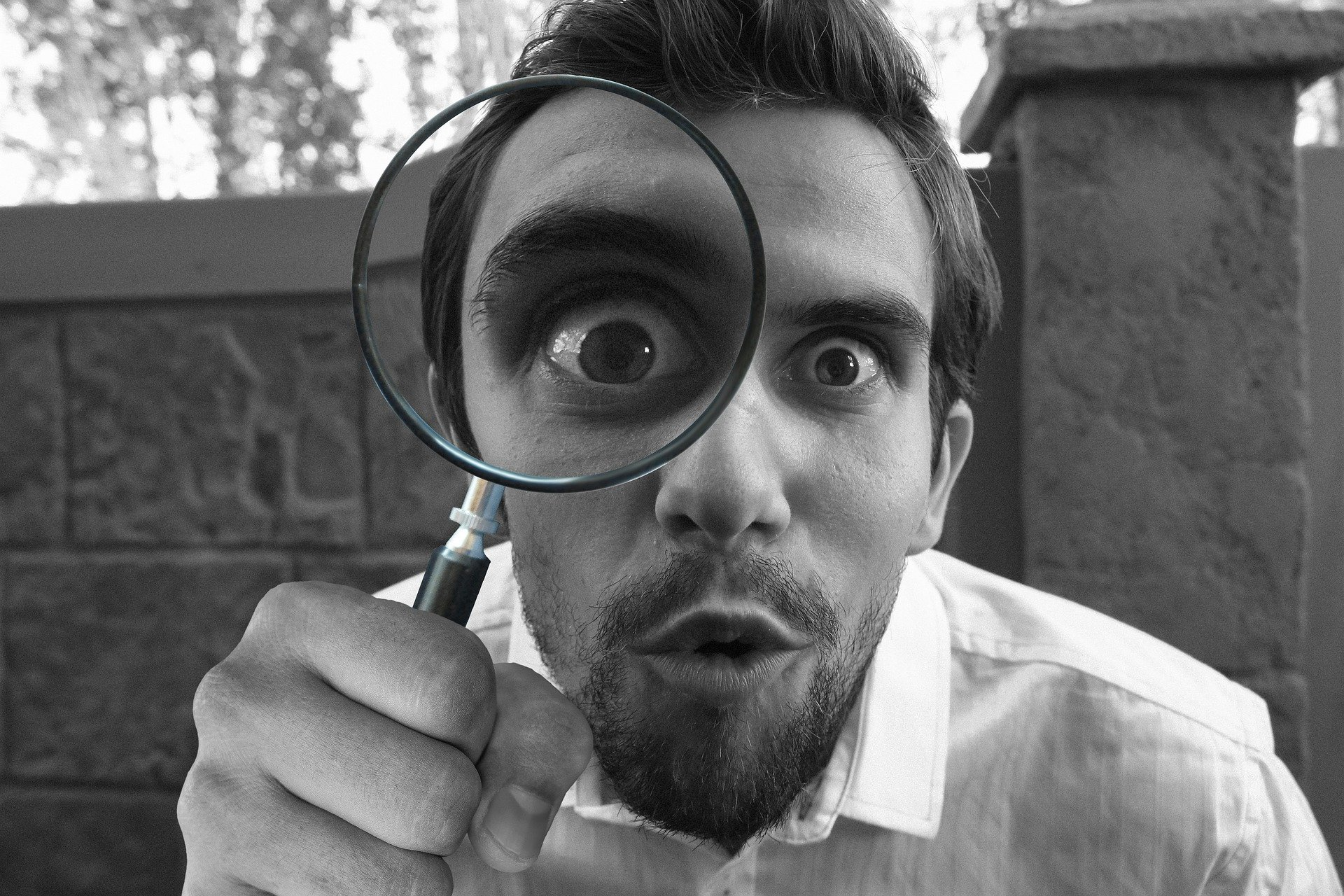 A man inspecting something with a magnifying glass. | Source: Pixabay.