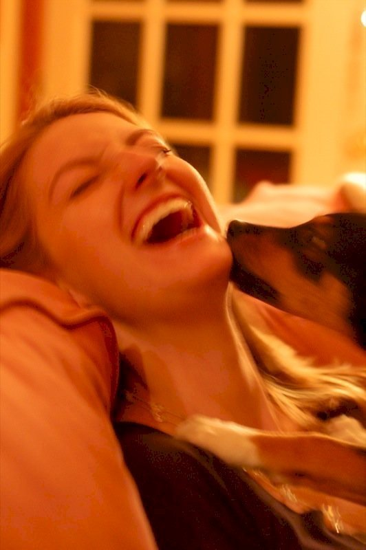 Une femme qui rit avec son chien. l Source: Wikimedia