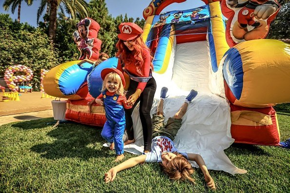 Christina Aguilera (C), her daughter Summer Rain Rutler (L) and son Max Liron Bratman smile and laugh as they slide down the play slide during the second birthday party for Christina Aguilera's daughter Summer Rain Rutler at a private residence on August 20, 2016, in Beverly Hills, California. | Source: Getty Images.