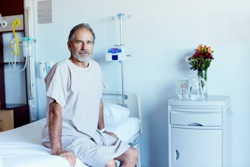A mature man sitting on bed in hospital ward | Photo: Getty Images