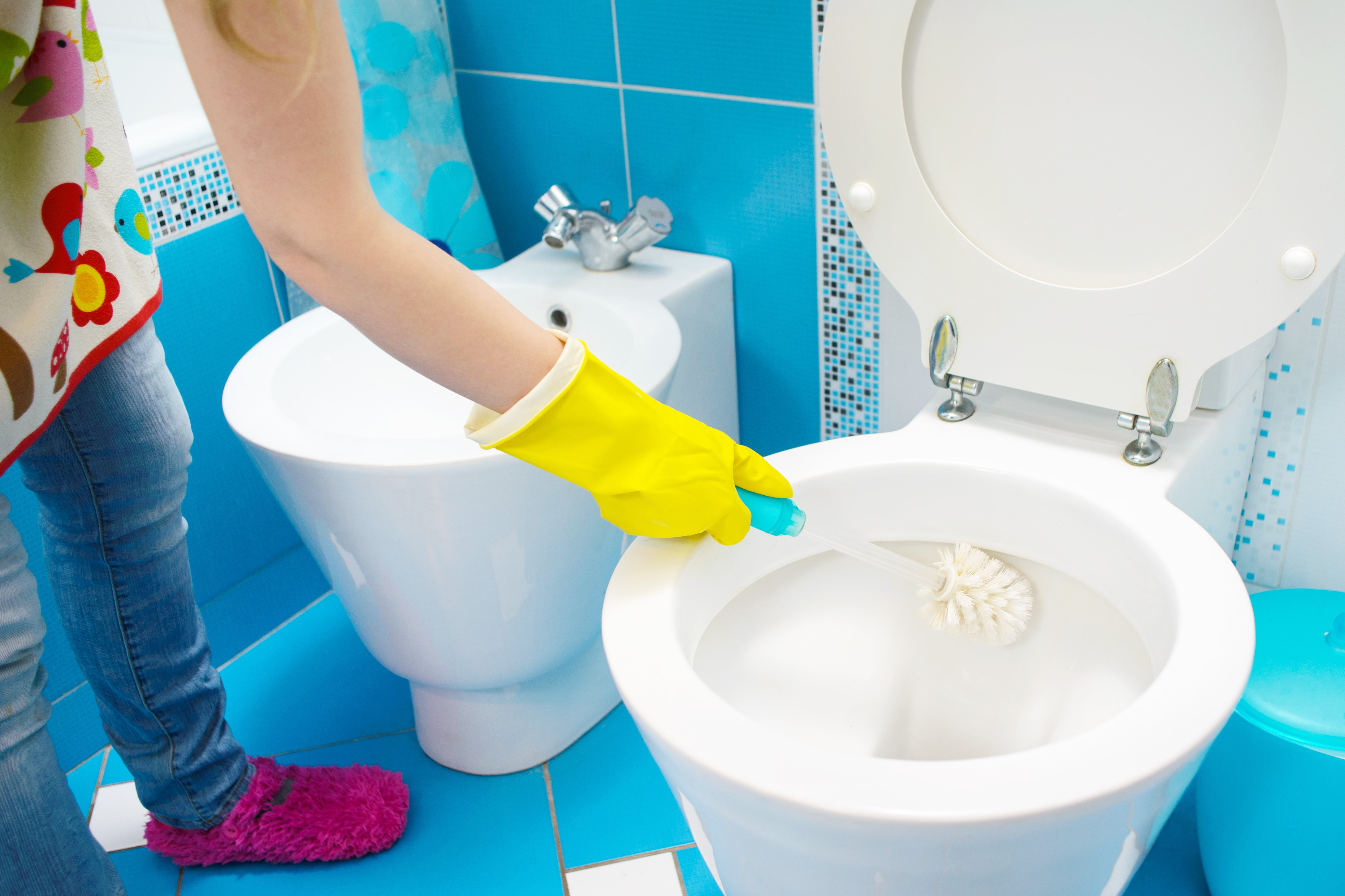 A woman cleans a bathroom toilet | Photo: Shutterstock