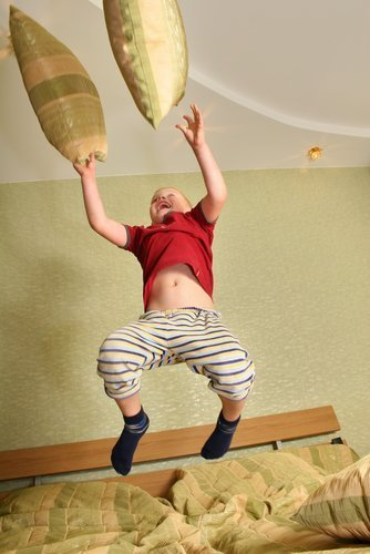 Boy jumping and playing on a bed. | Source: Shutterstock