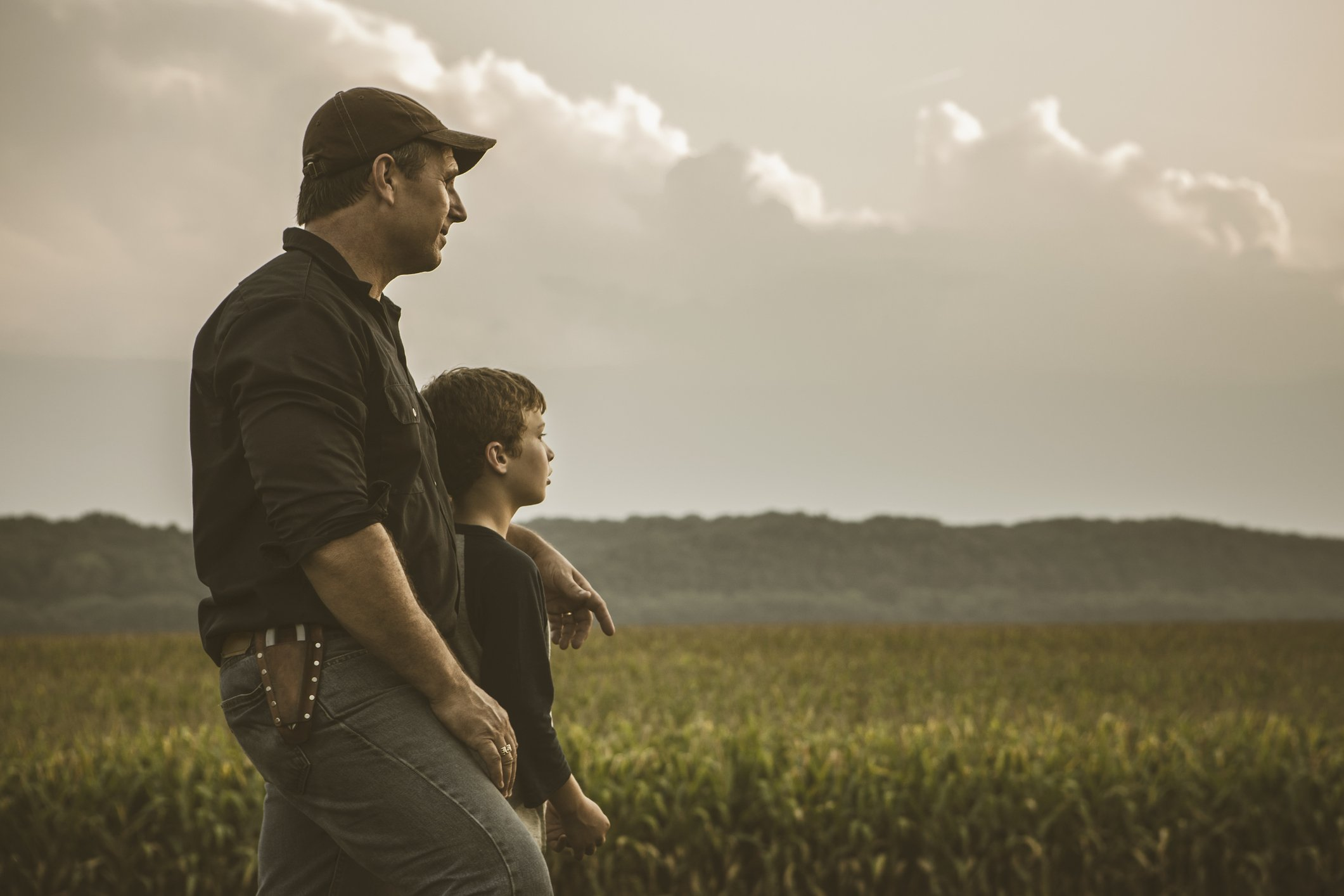 A photo of a father and son overlooking a crop field.   Photo: Getty Images