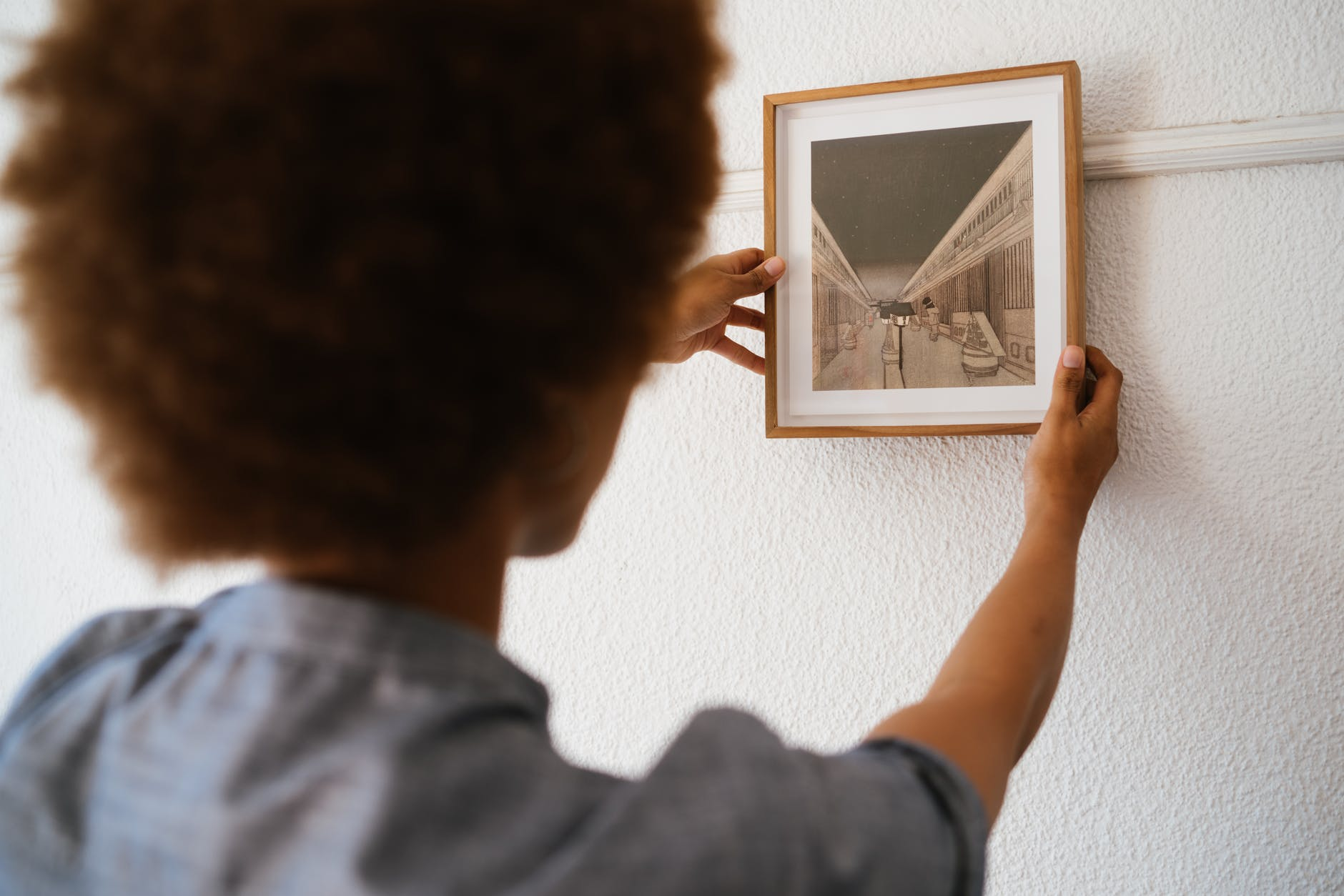 A woman hanging a framed picture on the wall. | Photo: Pexels