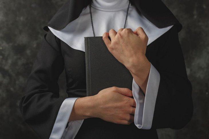 Monja sosteniendo un libro entre sus brazos.   Imagen: Shutterstock