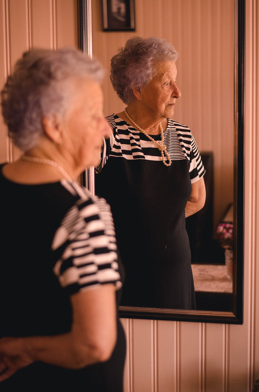 A mirror reflection of a sad senior woman. | Photo: Pexels