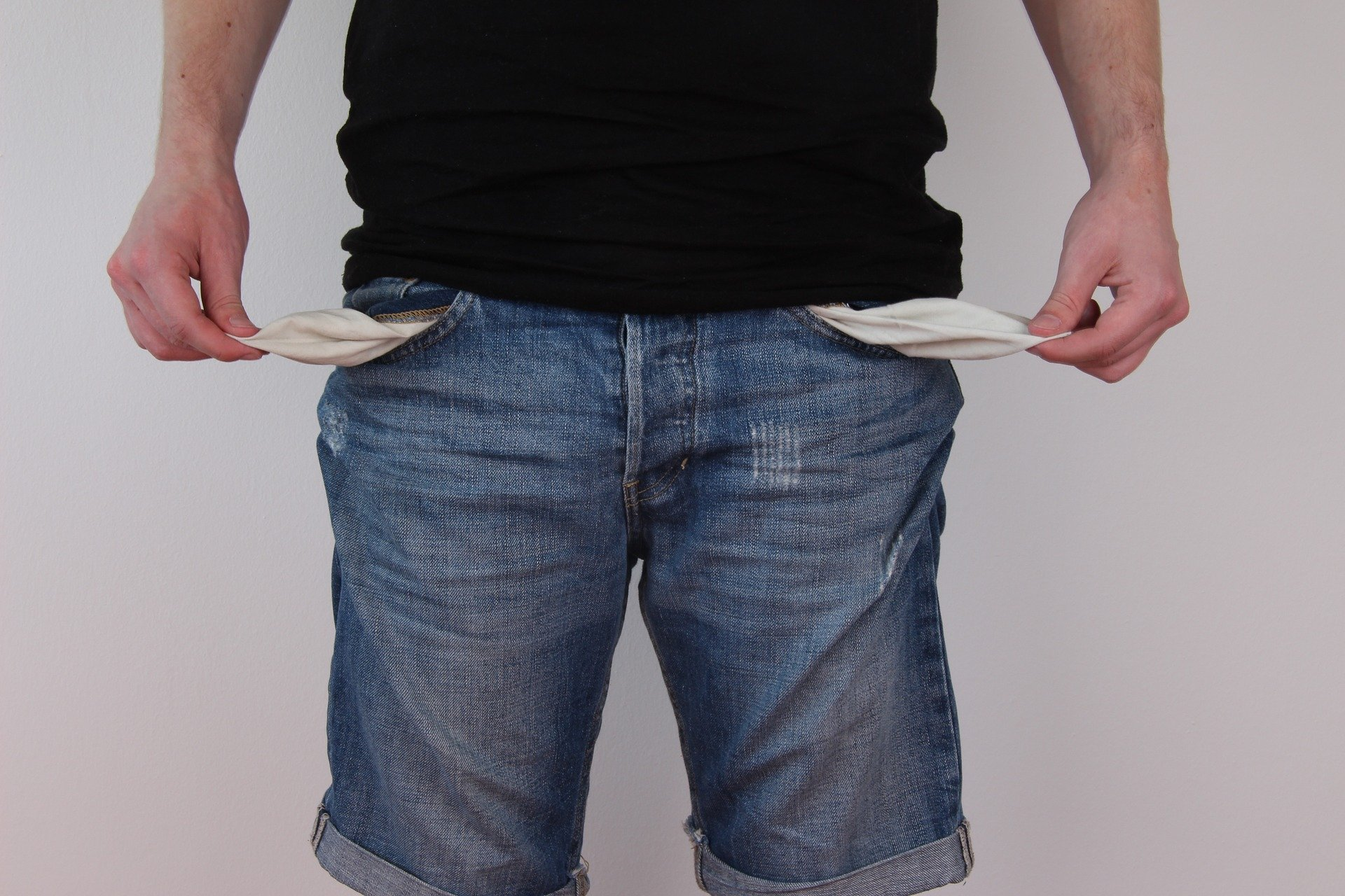 A broke young man shows his empty pockets.   Source: Pixabay.