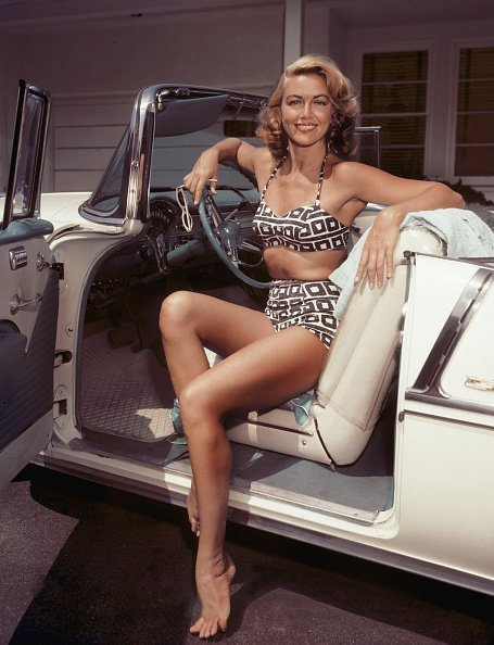American actress Dorothy Malone at the wheel of a cream-coloured convertible, circa 1955. | Photo: Getty Images
