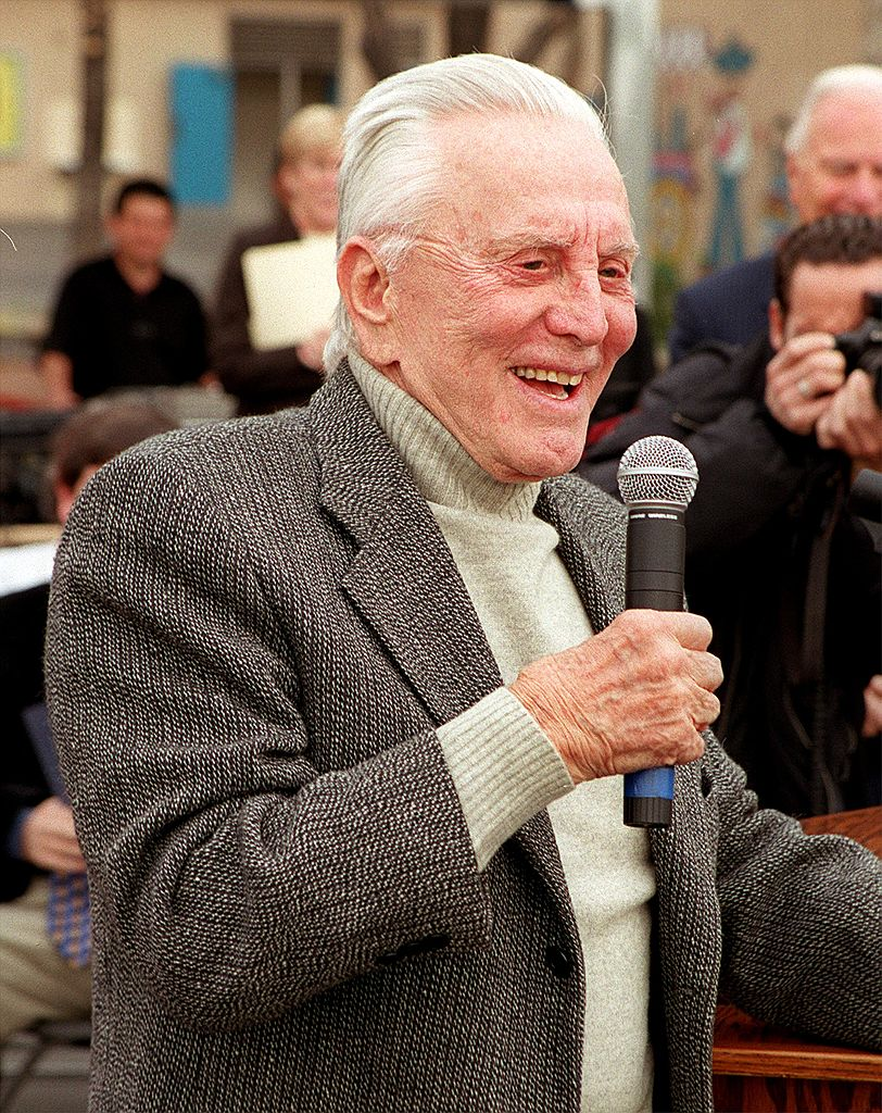 Kirk Douglas talks to students during the opening of the 100th playground that he has made possible through his donations | Photo: Getty Images