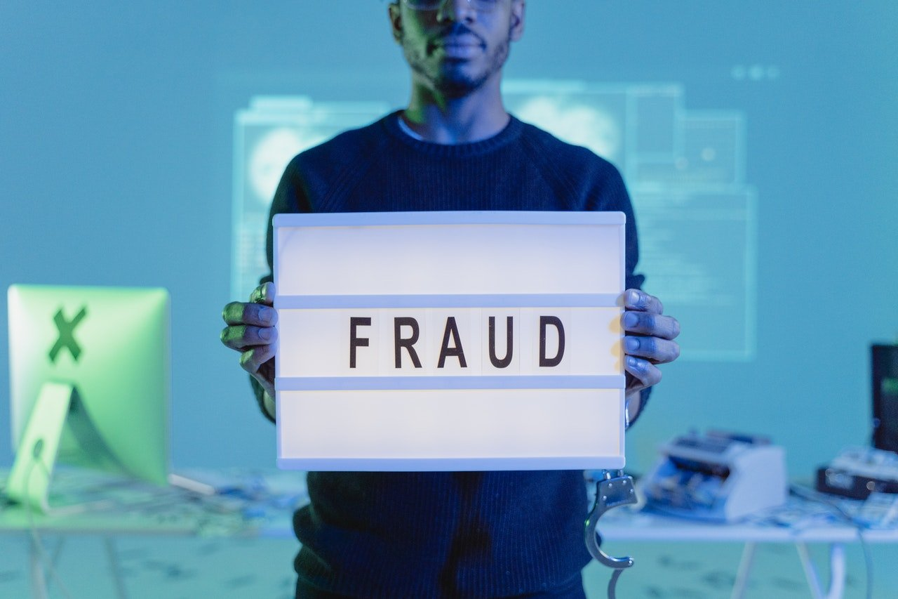 A man holding a board with fraud written on it | Photo: Pexels