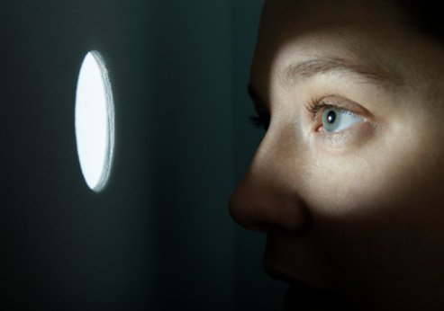 Woman looking through illuminated peep hole.| Photo: Getty Images