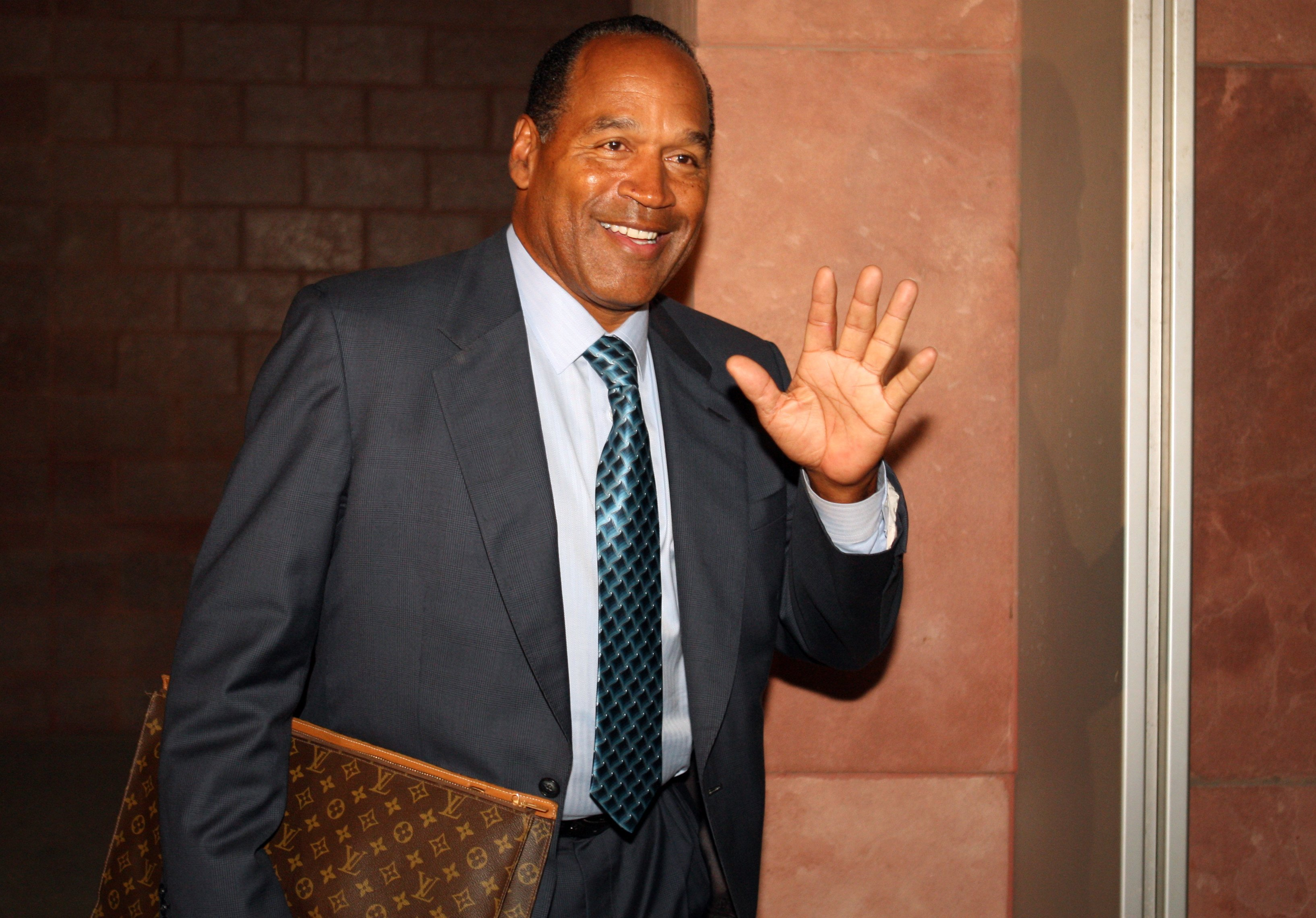 OJ Simpson waves at the press as he leaves the court after the closing arguments during his 2008 trial for felony kidnapping and armed robbery. | Photo: Getty Images
