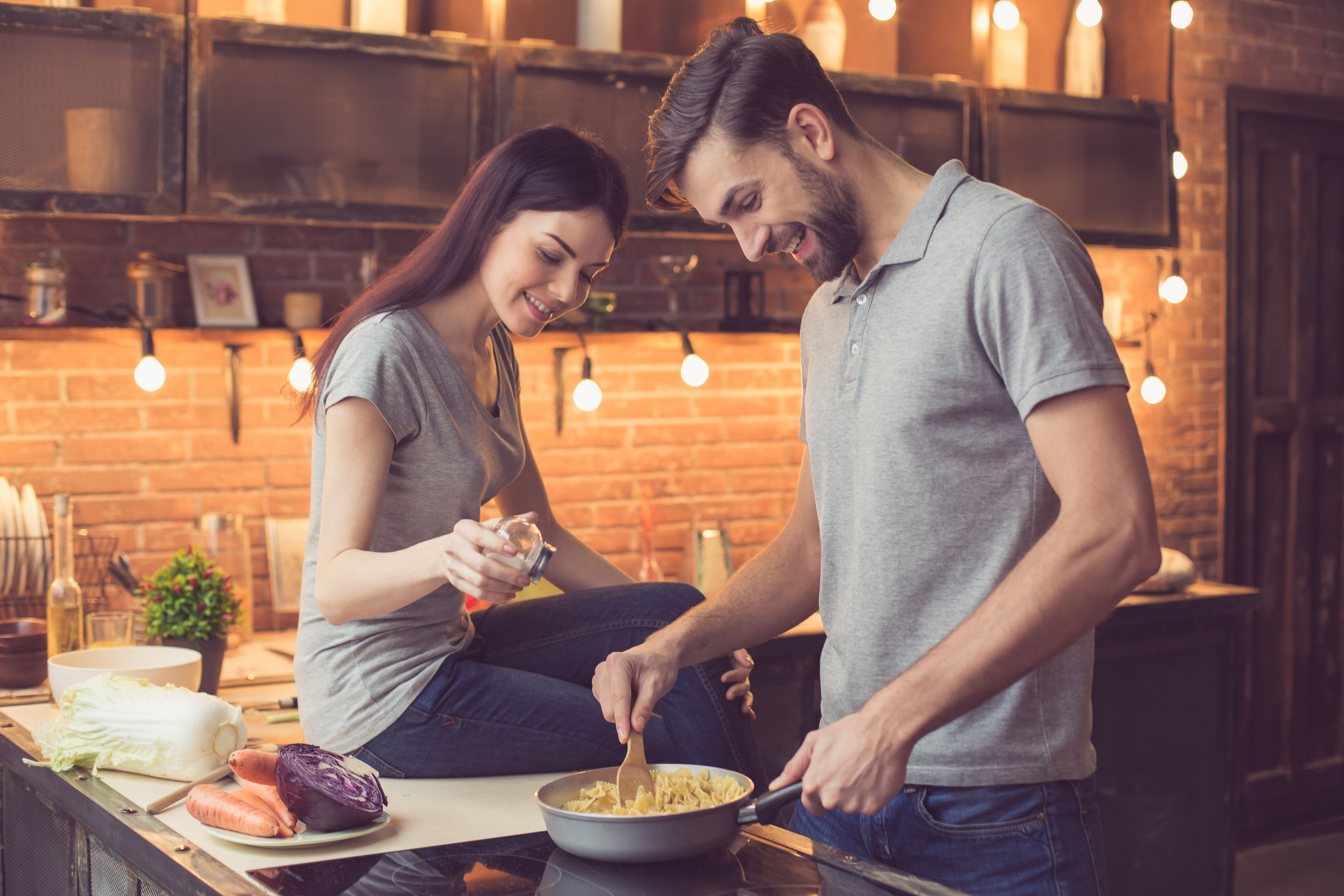 A couple cooking and talking in the kitchen. | Source: Shutterstock