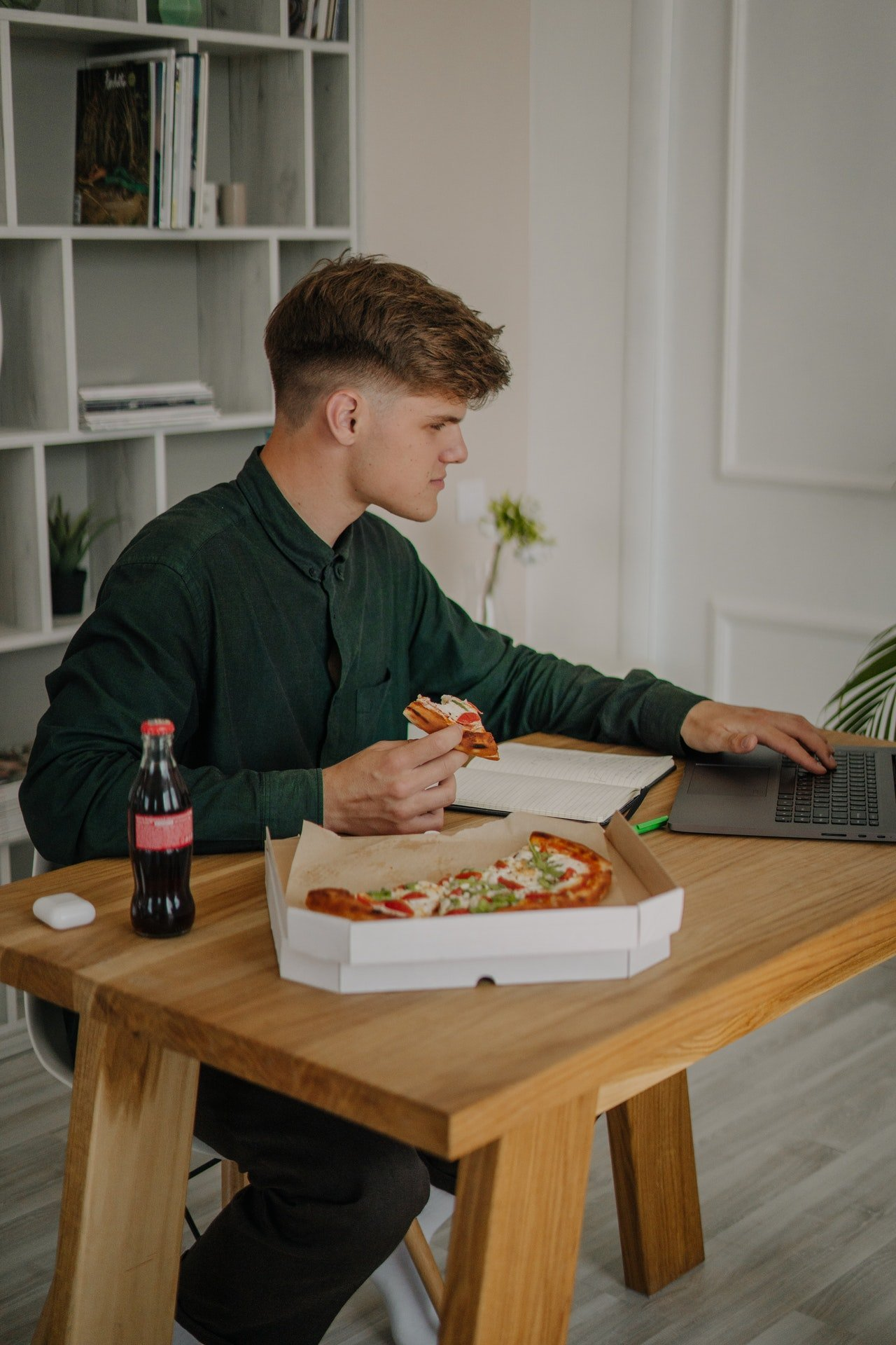 Photo of a man eating while working   Photo: Pexels