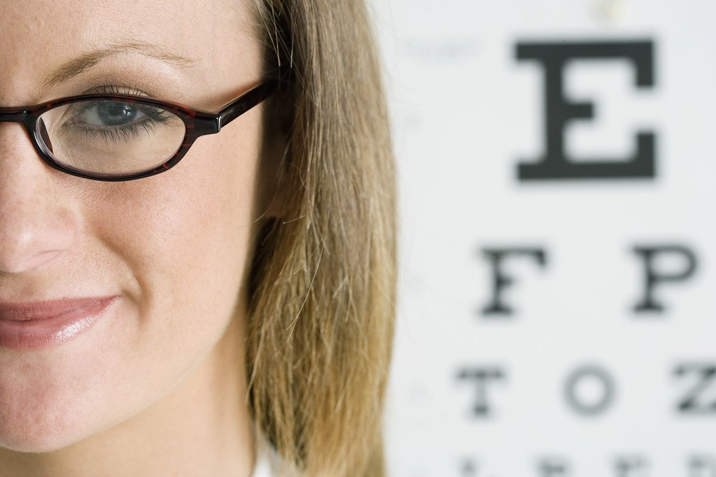 Lady with eyeglasses in front of an eye chart on April 20, 2013 | Photo: Flickr/Les Black