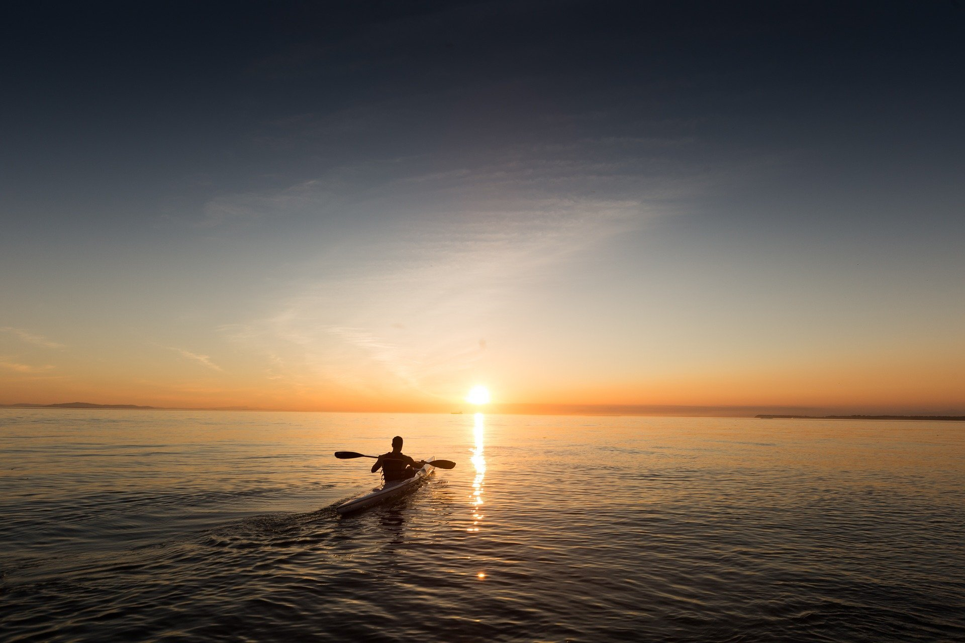 A silhouette of a person kayaking while the sun sets in front of him in the ocean | Photo: Pixabay/Free-Photos