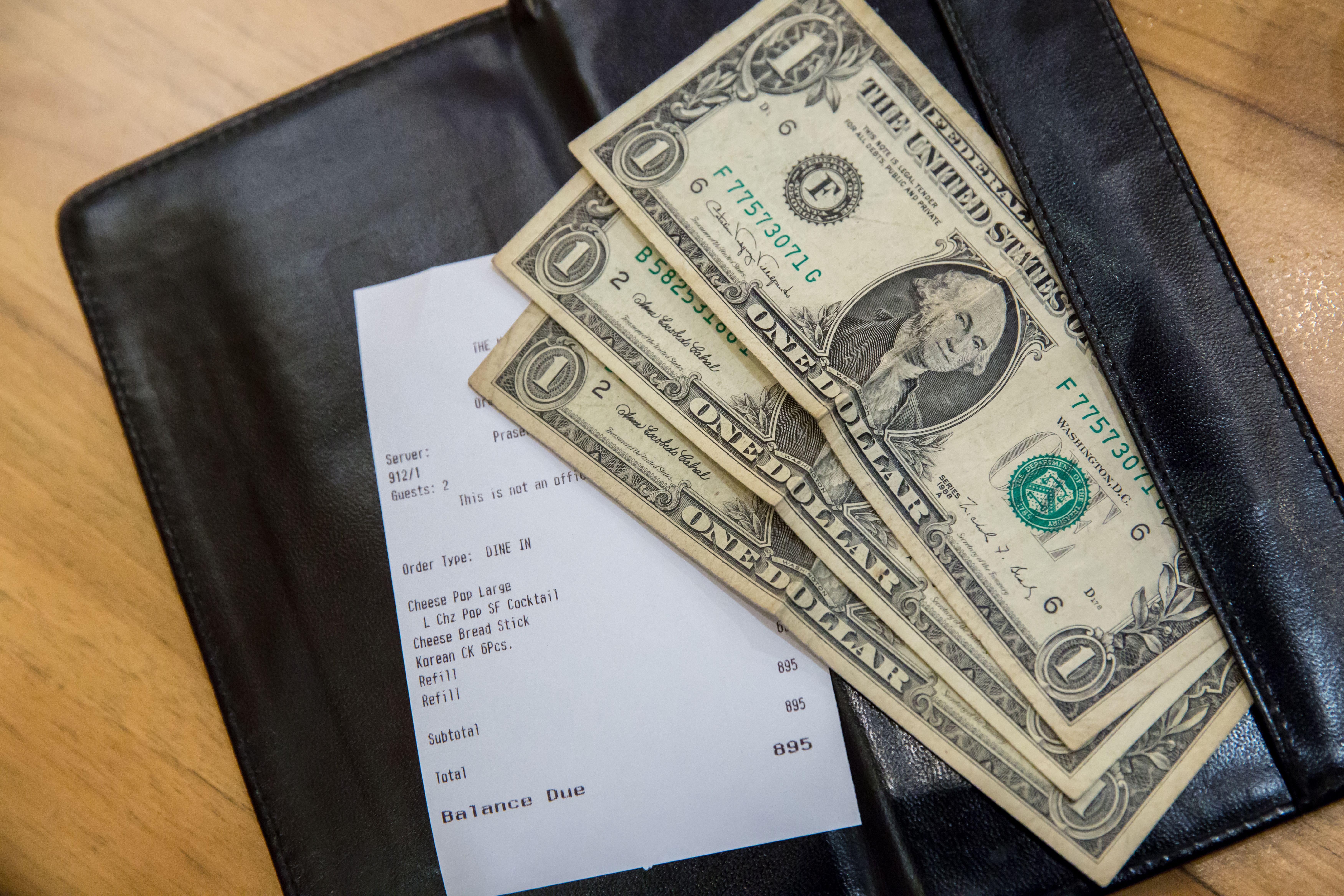 Dollar bills on top of a check.   Source: Shutterstock