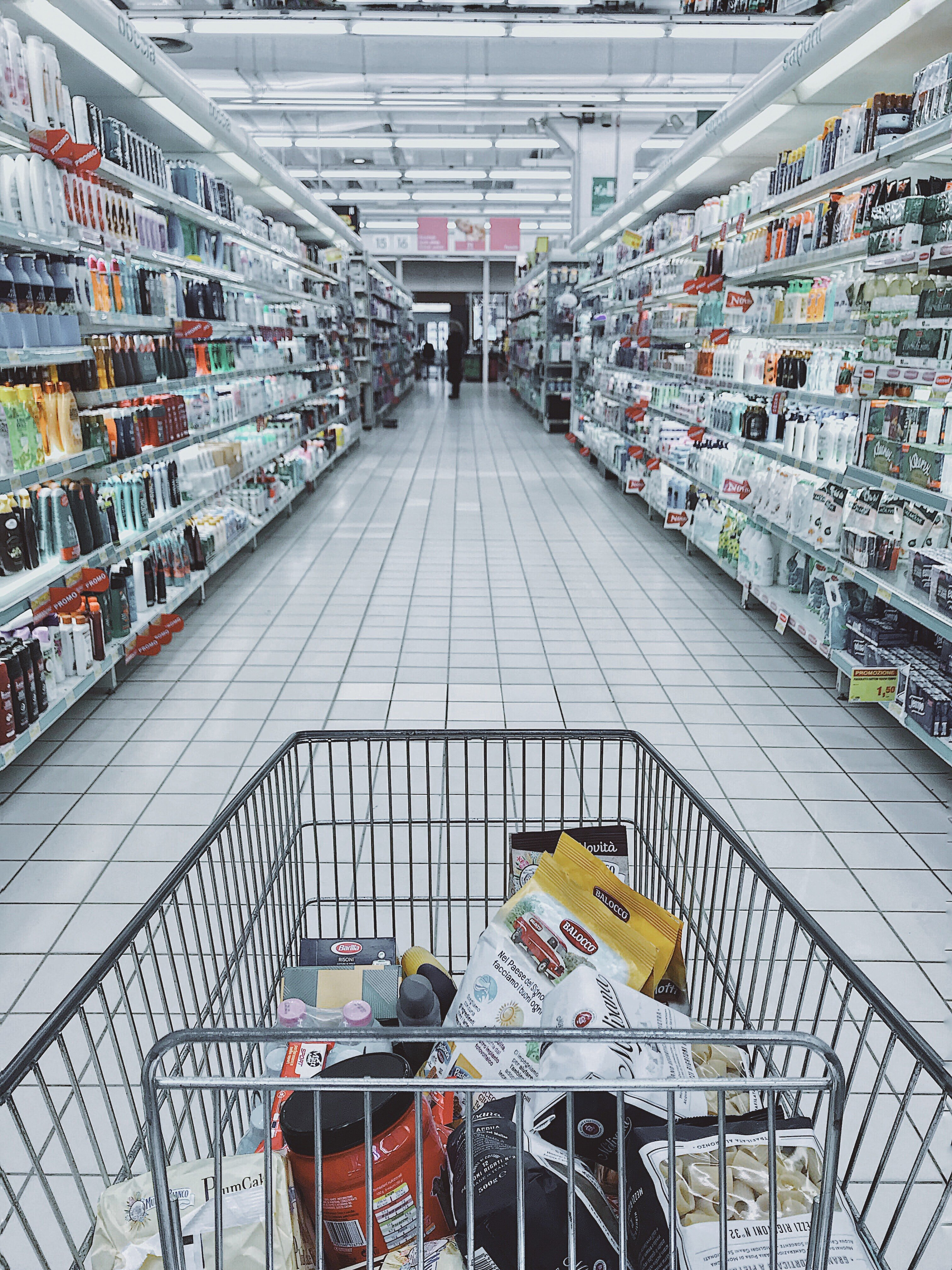 A cart standing in the aisle of a grocery store.   Pexles/ Oleg Magni
