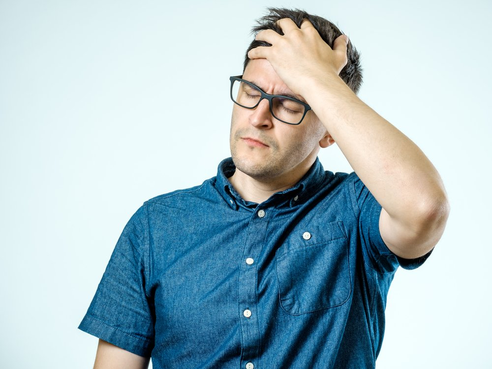A photo of a frustrated man holding his head. | Photo: Shutterstock