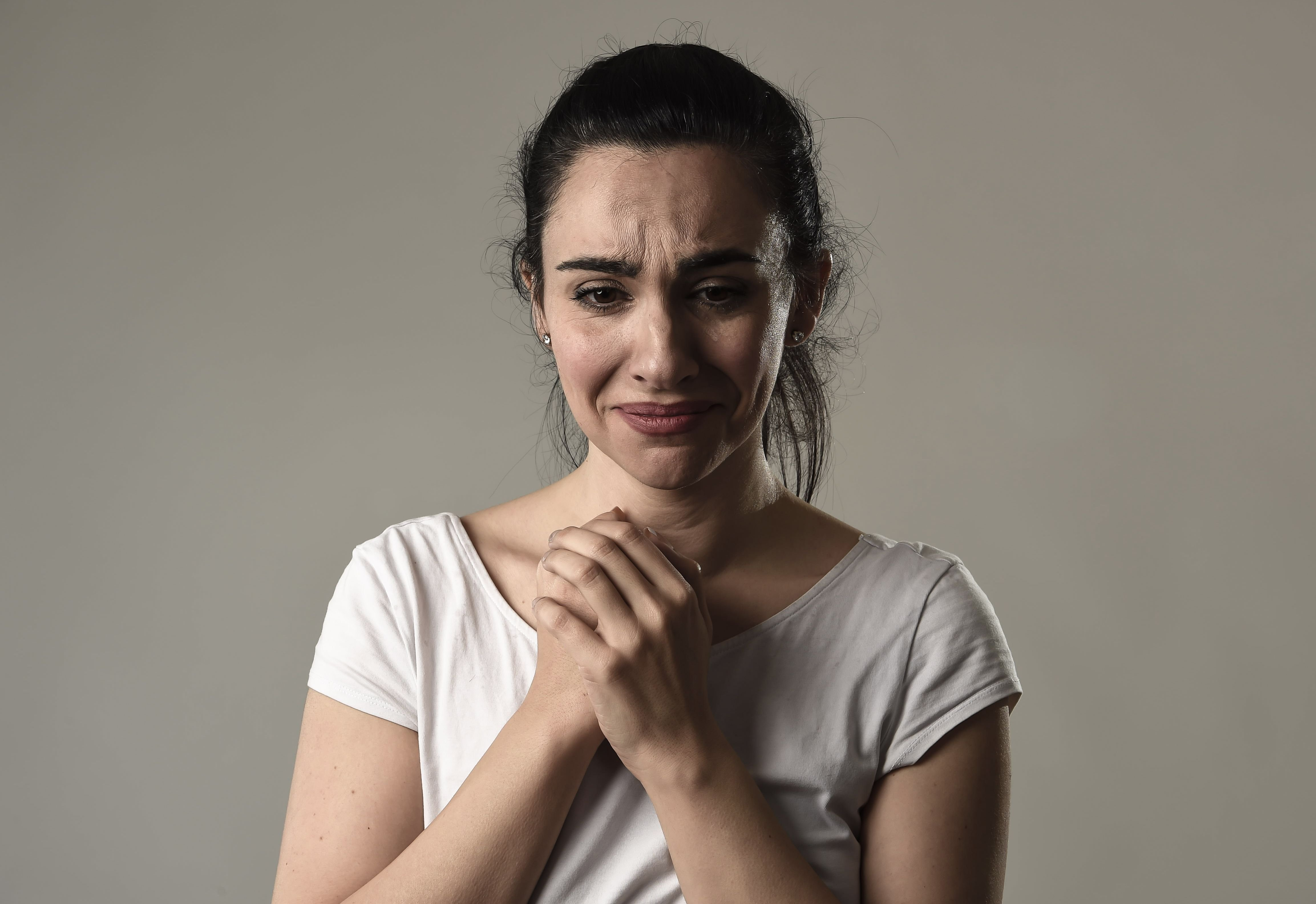 A woman clasps her hands together while looking sad.   Source: Shutterstock