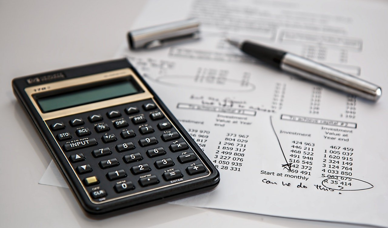 Black calculator and silver pen on a white piece of paper | Source: Pexels