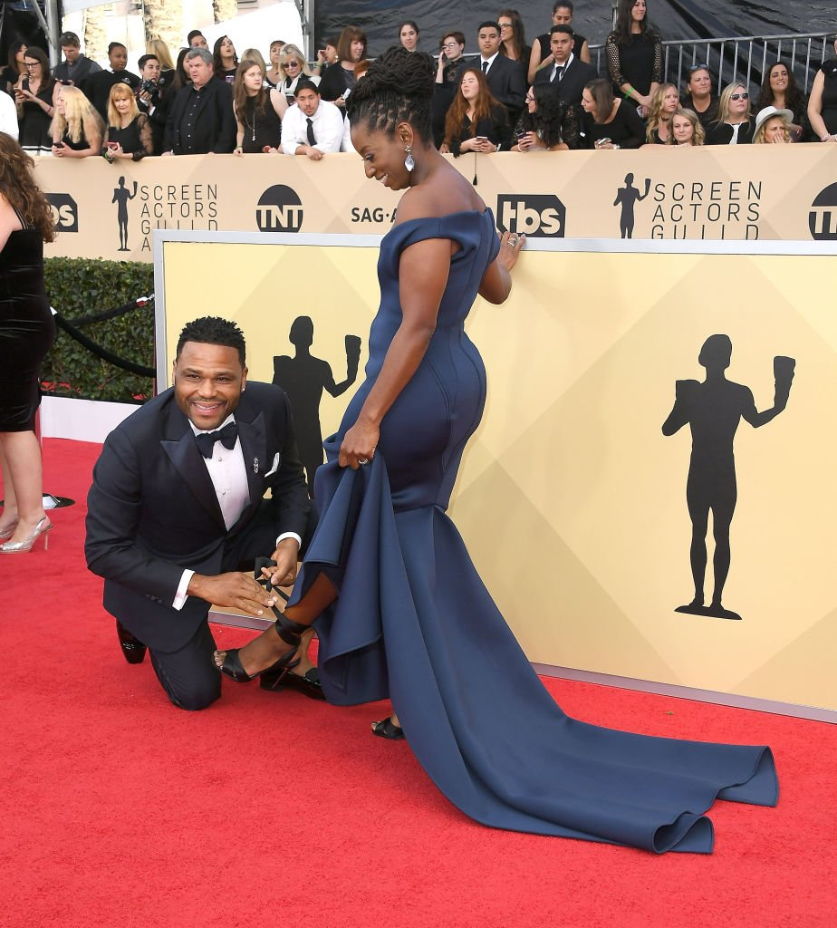 Anthony Anderson fixes his wife Alvina Stewart's shoe strap as they arrived at the 24th Screen Actors-Guild Awards on January 21, 2018, in Los Angeles, California | Source: Getty Images (Photo by Steve Granitz/WireImage)