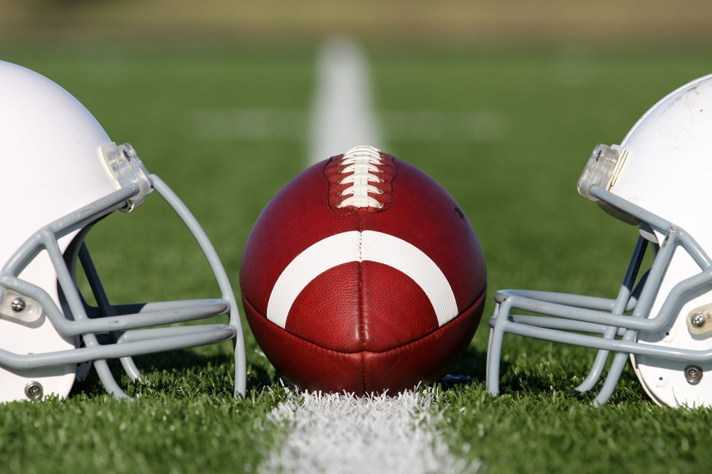 American Football and Helmets on the field. | Photo: Shutterstock