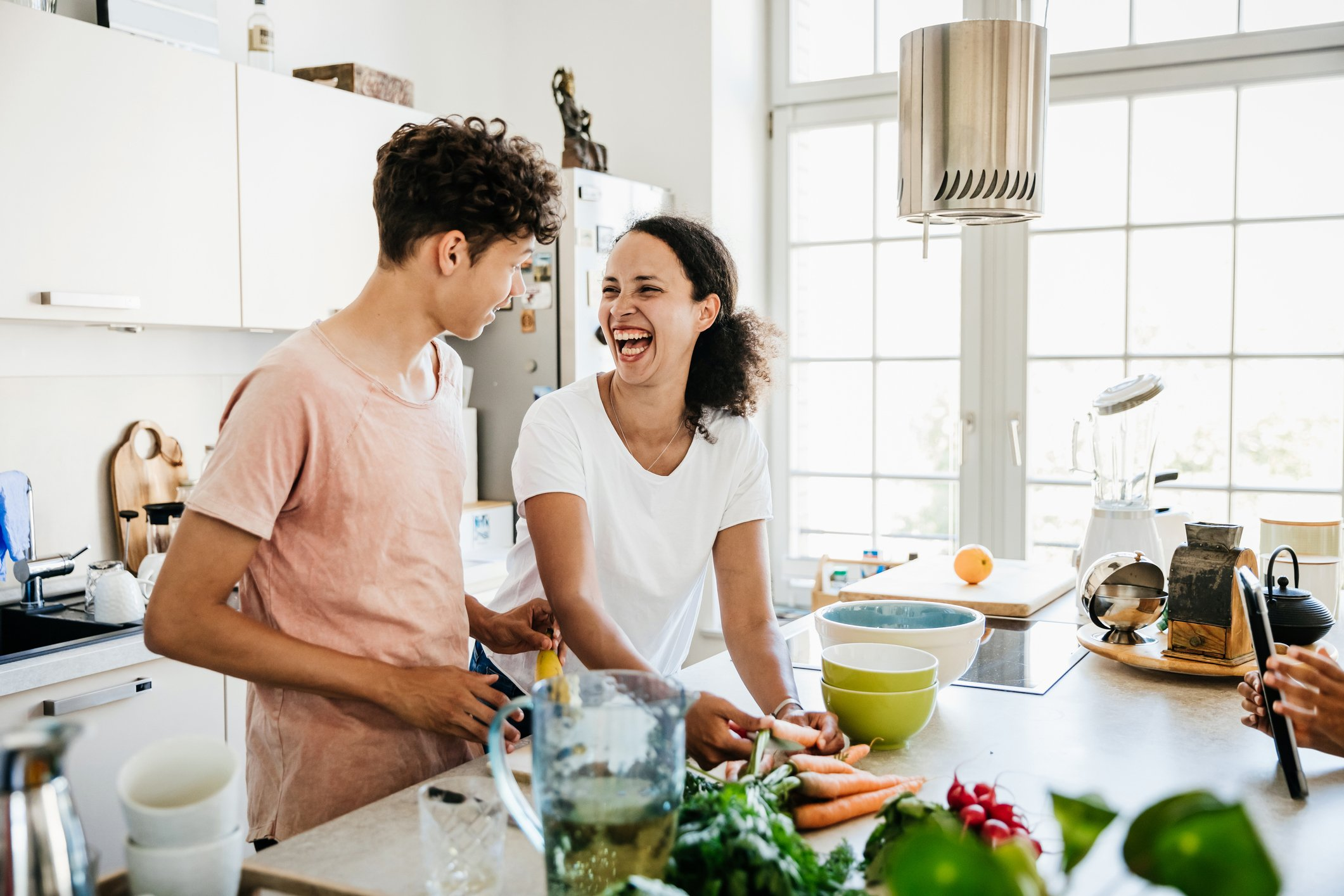 A single mom at home in the kitchen, laughing while preparing some lunch with her son.  Photo: Getty Images