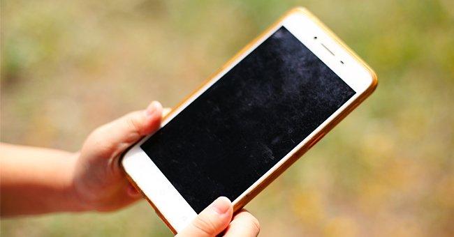 Un téléphone tenu dans une main | Photo : Shutterstock