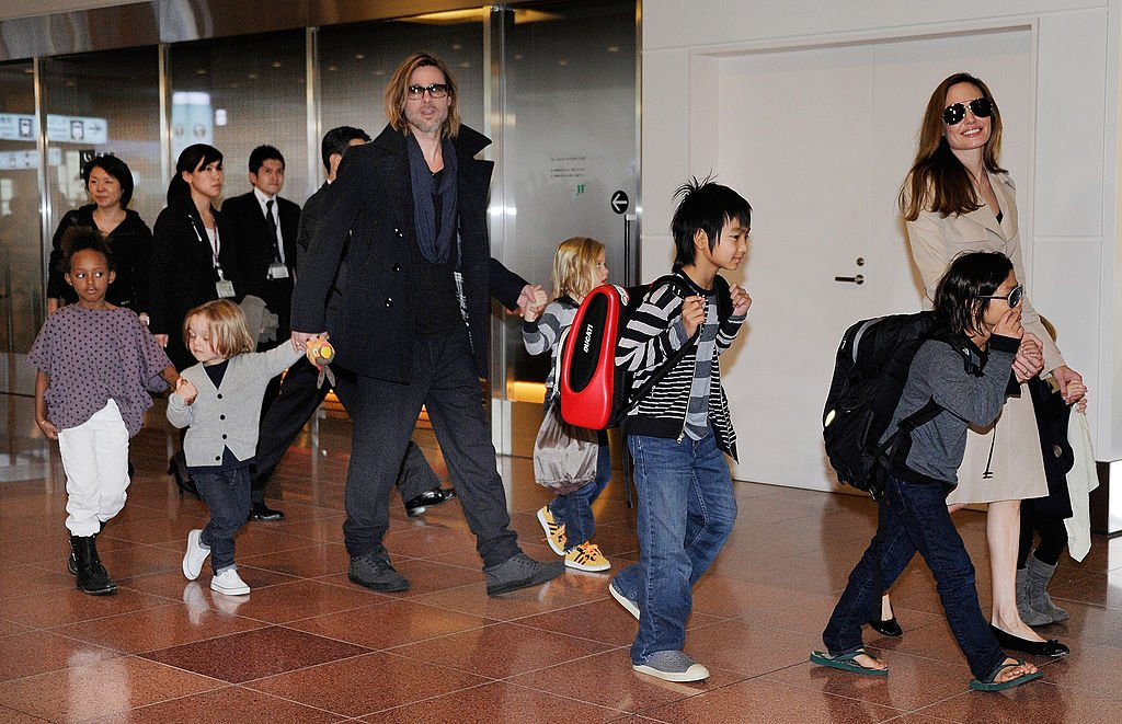 Accompanied by their six children, Brad Pitt and Angellina Jolie appear before photographers upon their arrival at Haneda Airport in Tokyo, November 2011   Source: Getty Images