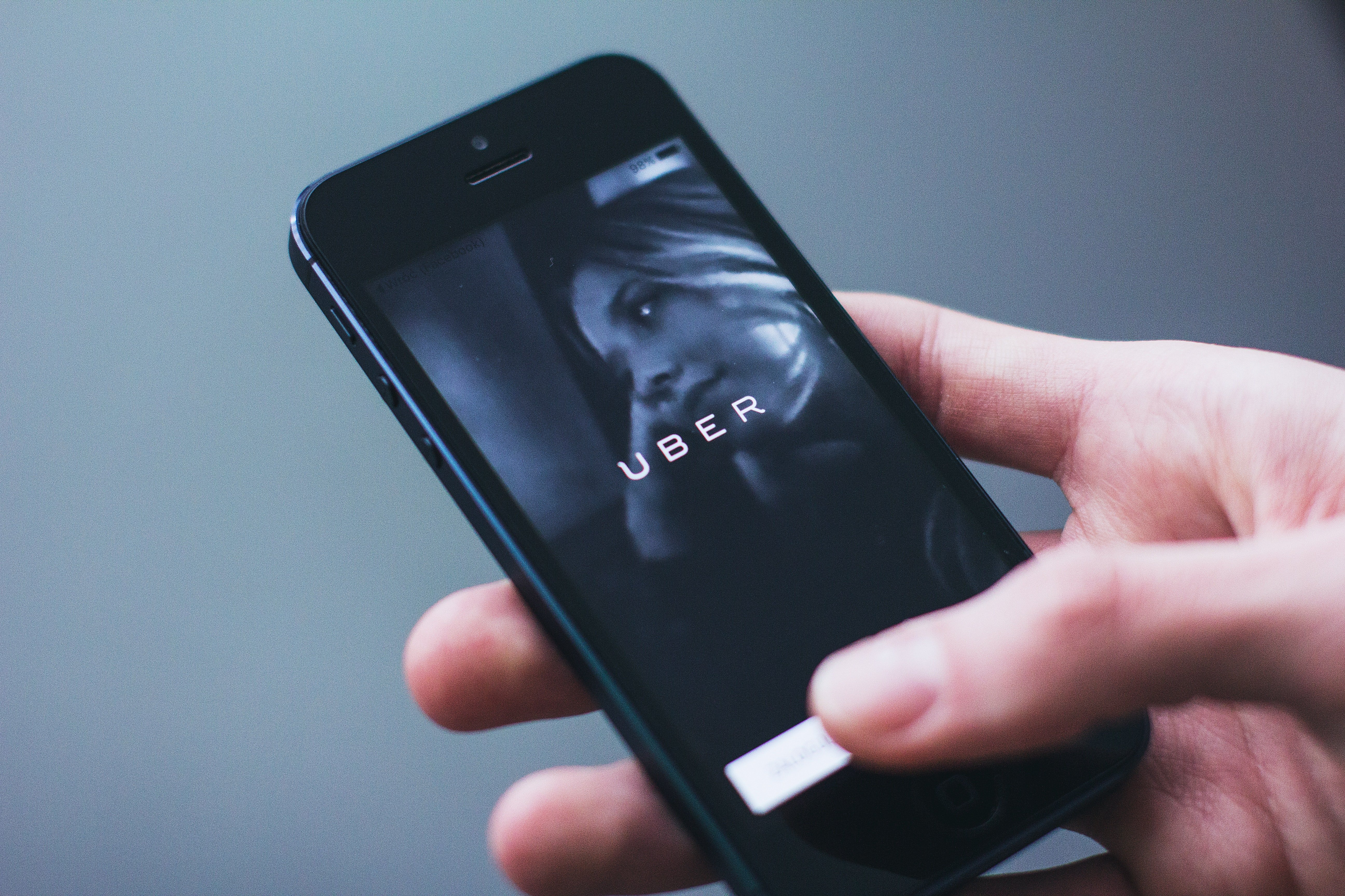 Hand holding mobile phone with Uber app. | Source: Pexels