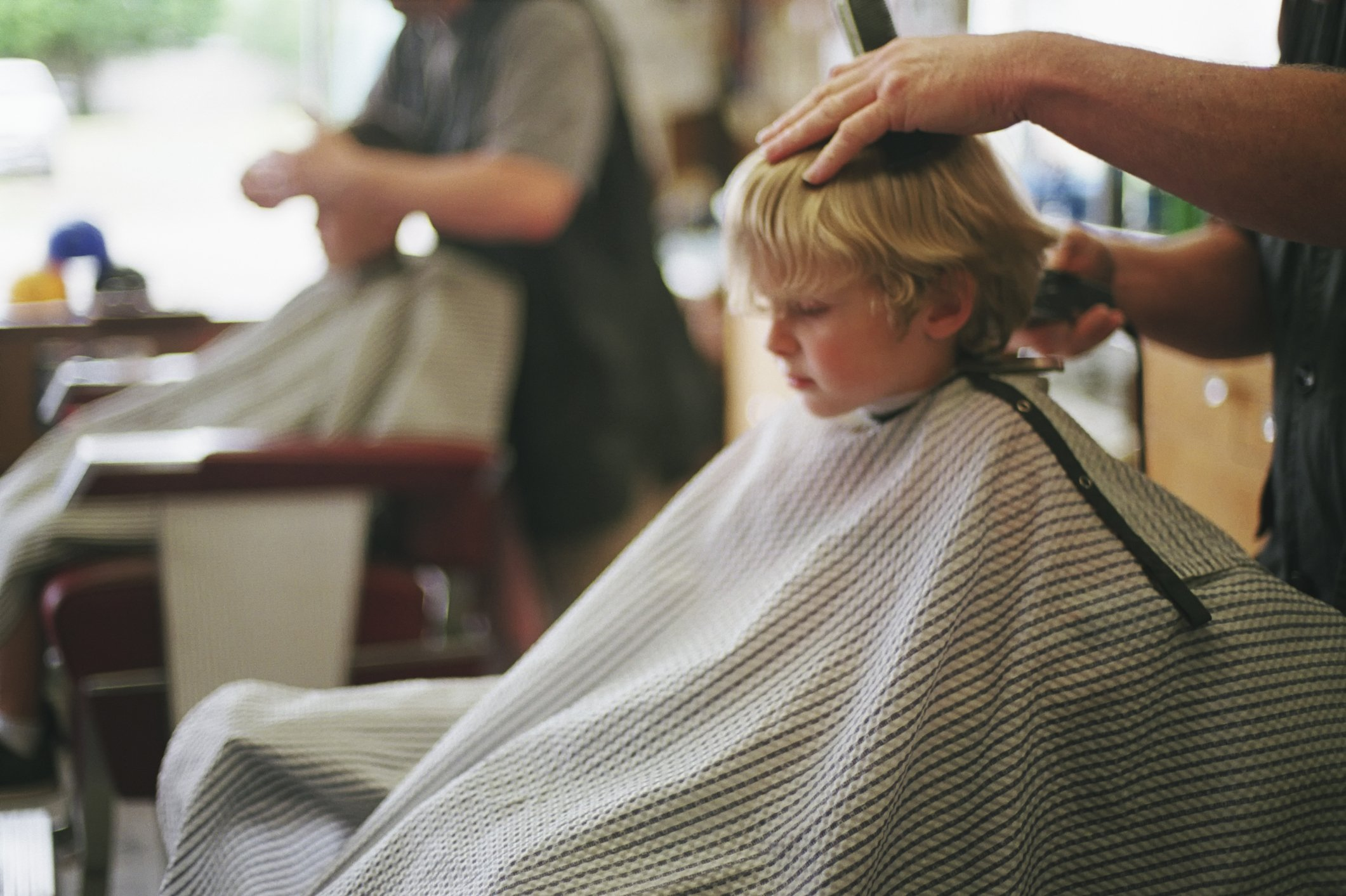 A young, five-year-old boy sits patiently while getting his hair cut at a local barbershop. | Photo: Getty Images