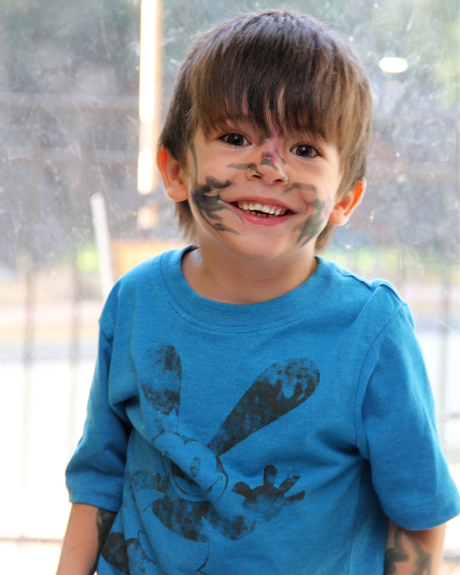 Pictured - A little boy with ink prints on his face smiles while having fun   Source: Pixabay