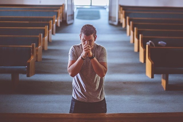 A man praying before God in a church. | Source: Pixabay