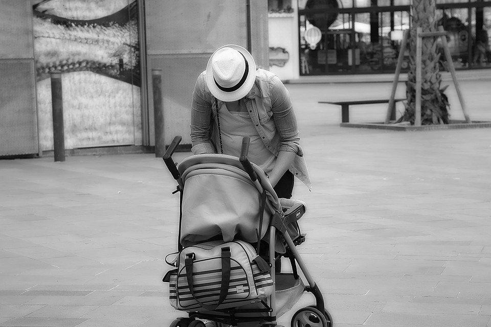 Une mère avec un chapeau devant la poussette | Photo: Pixabay