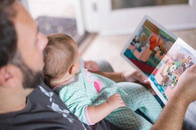 Man holding baby while reading a book | Source: Unsplash