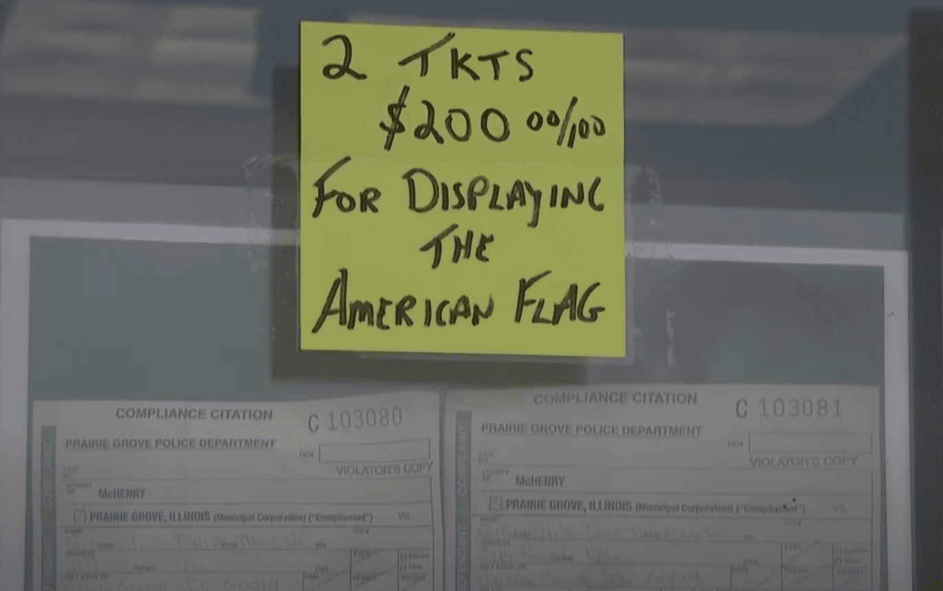 A business owner taped two tickets to the front door of his shop to notify customers about the citation he received for flying the American flag | Photo: Youtube/FOX 32 Chicago